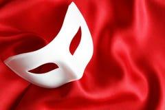 Venetian Mask On Red. White venetian mask lying on red silk background
