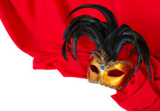 Venetian mask on red fabric. Venetian mask with black feathers on red fabric royalty free stock image