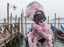 Venetian Mask with Rose. Venice, Italy- February 19th, 2012: Portrait of a person in a traditional mask posing with a rose near the gondolas dock in San Marco Royalty Free Stock Image