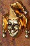 Venetian mask of smiling joker. Golden Venetian mask of smiling joker against stone background Stock Images