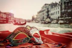 venetian maska na czerwonej jedwabniczej tkaninie przed rozmytym Wenecja Zdjęcia Royalty Free