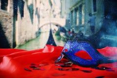 venetian maska na czerwonej jedwabniczej tkaninie przed rozmytym Wenecja Obraz Royalty Free