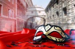 venetian maska na czerwonej jedwabniczej tkaninie przed rozmytym Wenecja Obrazy Stock