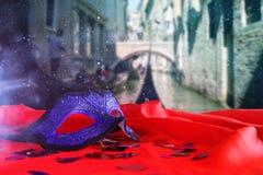 venetian maska na czerwonej jedwabniczej tkaninie przed rozmytym Wenecja Zdjęcia Stock