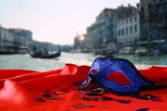 venetian maska na czerwonej jedwabniczej tkaninie przed rozmytym Wenecja Zdjęcie Stock