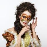 venetian maskering Härlig kvinna i tappningklänning och en maskering på högt Royaltyfri Fotografi