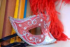 Venetian maskeringssouvenir på en bokhylla Royaltyfri Foto