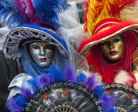Venetian Masks. Venice, Italy- February 18th, 2012: Environmental portrait of two persons wearing nice colorful costumes and masks during the Venice Carnival Royalty Free Stock Photo