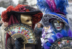 Venetian Masks. Venice, Italy- February 18th, 2012: Environmental portrait of two persons wearing nice colorful costumes and masks during the Venice Carnival Stock Images