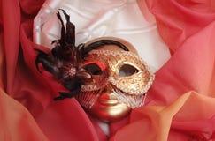Venetian masks. Golden venetian masks on a textile Royalty Free Stock Image