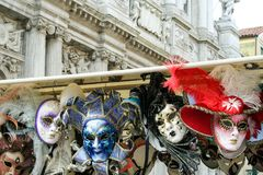 Venetian masks. Hanging with a baroque architecture on the background Royalty Free Stock Photo