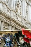 Venetian masks. Hanging with a baroque architecture on the background Stock Photos