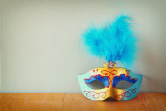 Venetian masquerade mask on wooden table. retro filtered image Stock Photography