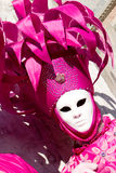 A venetian in a pink costume. And white mask Stock Photo