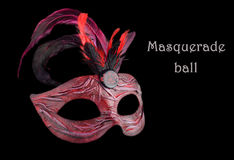 Venetian red Carnival half mask with feathers, at black background. Royalty Free Stock Image