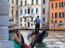 Venetian story. Venice,Italy,July 28th 2011:A girl sitting on the edge of the Grand Canal in Venice,taking a picture of a gondolier using a smart phone Royalty Free Stock Photography