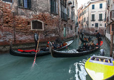 Venetian Traffic. Venice,Italy- February 18, 2012:Three gondolas full of tourists cruise on a narrow canal between buildings in Venice, durign the Carnival days Royalty Free Stock Photography