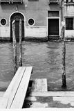 Venetian view with canal and small jetty. Venice, Italy. Black and white royalty free stock photo