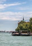 Venetian Waterbus Station. Venice, Italy- July 28,2011:  Image of a specific waterbus (vaporetto) with tourists stoping in the Sacca Fisola station on a canal in Royalty Free Stock Photos