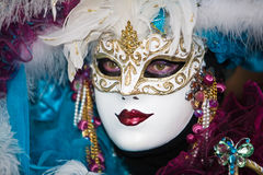 Venetian wearing a white mask with red lips Royalty Free Stock Photos