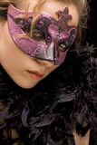 Venetian woman. Portrait of mysterious blond woman wearing purple stylish carnival mask and black feathers, role play Royalty Free Stock Photo