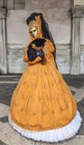 Venetian Yellow Costume. Venice, Italy- February 19th, 2012: A person disguised in a beautiful yellow Venetian disguise posing in San Marco Square during the Royalty Free Stock Photography