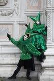 2 venetianische Karnevals-Zahlen in bunten grünen und schwarzen Kostümen und in Masken Venedig Italien stockbilder