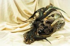 Venetianische Karnevalsmaske auf einem hellen Gewebehintergrund Lizenzfreie Stockfotos