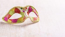 Venetianische Karnevalsmaske auf hellem hölzernem Hintergrund Lizenzfreies Stockfoto