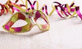 Venetianische Karnevalsmaske mit Papierschlange auf hellem hölzernem Hintergrund Stockfotos