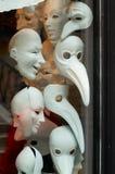 Venetianische Masken, die in einem Schaufenster (Venedig, hängen) Stockfotos