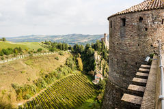 Venetians medieval Fortress in Brisighella. The brickwalls of the medieval Fortress of Venetians in Brisighella. Cultivated fields and the Clock Tower in the Stock Image