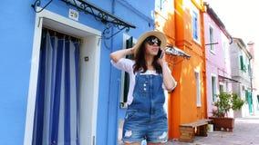 Veneza, Burano, Itália - 7 de julho de 2018: jovem mulher, menina em vidros de sol, chapéu, short, falando no telefone, sorrindo video estoque