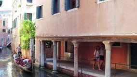 VENEZA, ITÁLIA - 8 DE AGOSTO DE 2017 Pares novos que andam ao longo do canal Venetian com gôndola famosa Imagem de Stock Royalty Free