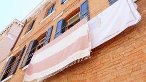 Veneza, Itália - 7 de julho de 2018: a arquitetura velha bonita de Veneza, uma casa com os obturadores azuis velhos, roupa é seca vídeos de arquivo