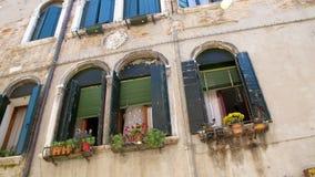 Veneza, Itália - 7 de julho de 2018: arquitetura velha bonita de Veneza, de uma casa com os obturadores e as flores verdes velhos filme