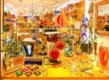 Veneza, Itália - 4 de maio de 2017: A loja com lembranças tradicionais e os presentes gostam de Murano de vidro à visita dos turi Imagem de Stock