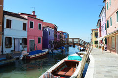 Venezia Burano con le suoi case, barche e ponte variopinti tipici nel pomeriggio soleggiato, Venezia Fotografia Stock Libera da Diritti