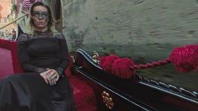 VENEZIA, ITALIA - 19 GIUGNO 2016: Bella donna in vestito nero con la guida carnaval della maschera sulla gondola, Venezia stock footage
