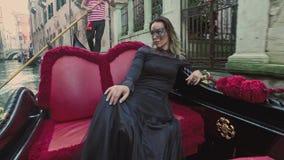 VENEZIA, ITALIA - 19 GIUGNO 2016: Bella donna in vestito nero con la guida carnaval della maschera sulla gondola, Venezia video d archivio