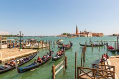 VENEZIA, ITALIA - 4 LUGLIO 2018: Bella vista delle gondole tradizionali vicino a San Marco con Basilica di storica Santa fotografia stock libera da diritti