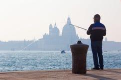 VENEZIA, ITALIA - 14 MARZO 2014: Pescatore da lungomare di Riva S Lungomare di Biagio e siluetta della chiesa di Santa Maria dell Fotografia Stock