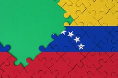 Venezuela flag is depicted on a completed jigsaw puzzle with free green copy space on the left side.  royalty free stock photo