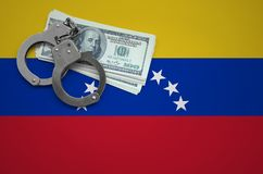 Venezuela flag with handcuffs and a bundle of dollars. The concept of breaking the law and thieves crimes.  royalty free stock photos