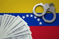 Venezuela flag with handcuffs and a bundle of dollars. The concept of illegal banking operations in US currency.  stock photo