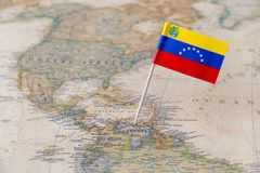 Venezuela flag pin on map. Paper flag pin of Venezuela on a world map showing neighboring countries. Officially the Bolivarian Republic of Venezuela is a Royalty Free Stock Image