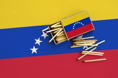 Venezuela flag is shown on an open matchbox, from which several matches fall and lies on a large flag.  royalty free stock photography