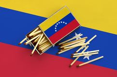 Venezuela flag is shown on an open matchbox, from which several matches fall and lies on a large flag.  royalty free stock photo