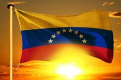 Venezuela flag weaving on the beautiful orange sunset with clouds background. Venezuela flag weaving on the beautiful orange sunset background stock photography