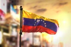 Venezuela flagga mot suddig bakgrund för stad på soluppgång Backli royaltyfria foton
